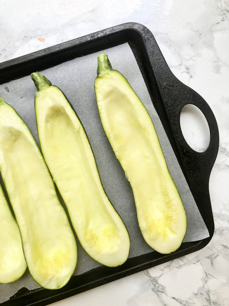A baking sheet with Zucchini Made into Zucchini Boats ready to be stuffed