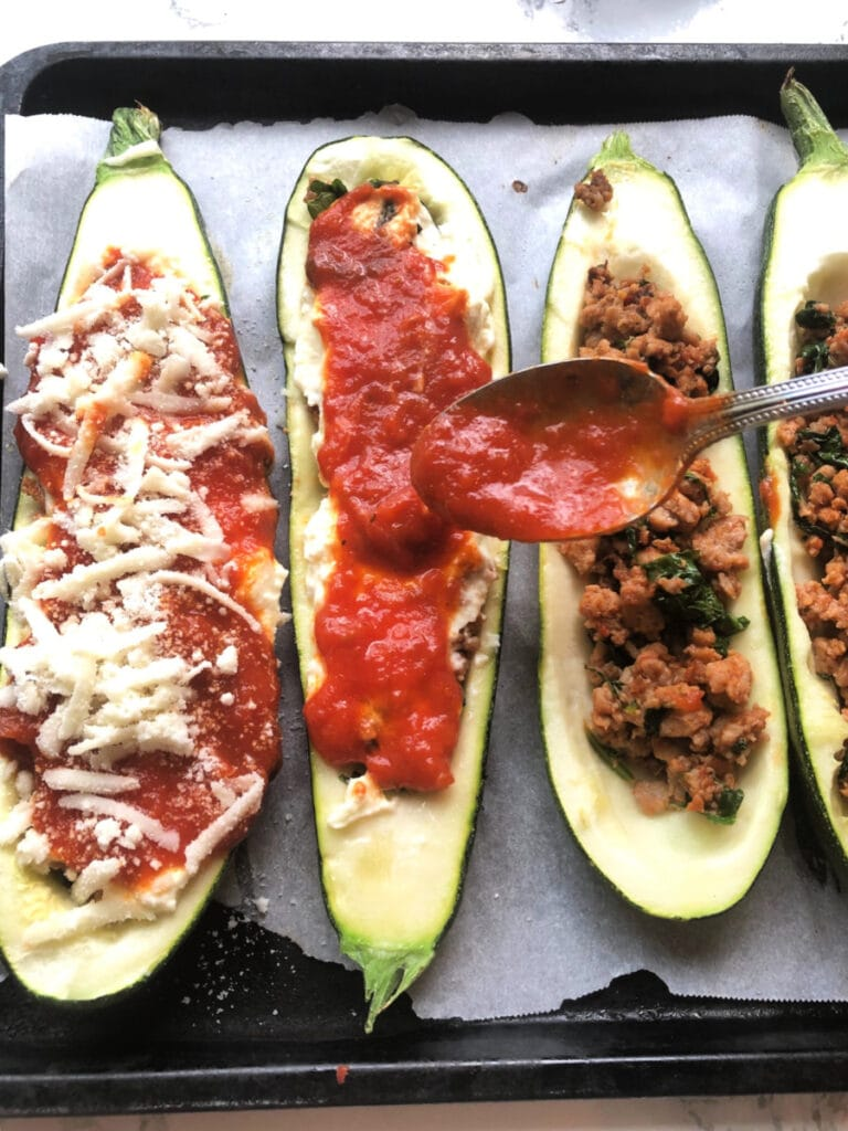 Spooning sauce over Lasagna Stuffed Zucchini Boats