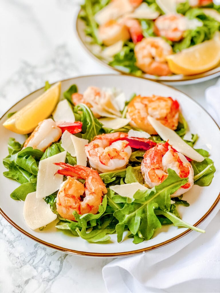 High angle photo of arugula salad with shrimp on a white plate. There is a second arugula salad recipe in the background, out of focus.