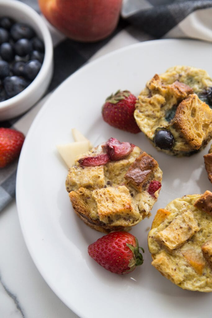 Overhead photo of Mini French Toast cups with fruit toppings and whole strawberries, on a white plate. Off to the side are whole strawberries, a peach, and a ramekin of blueberries, half out of frame.