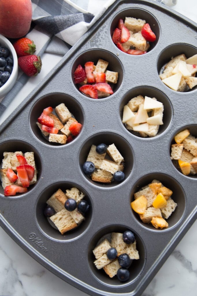 A muffin tin filled with healthy french toast casserole cups topped with various fresh fruit toppings