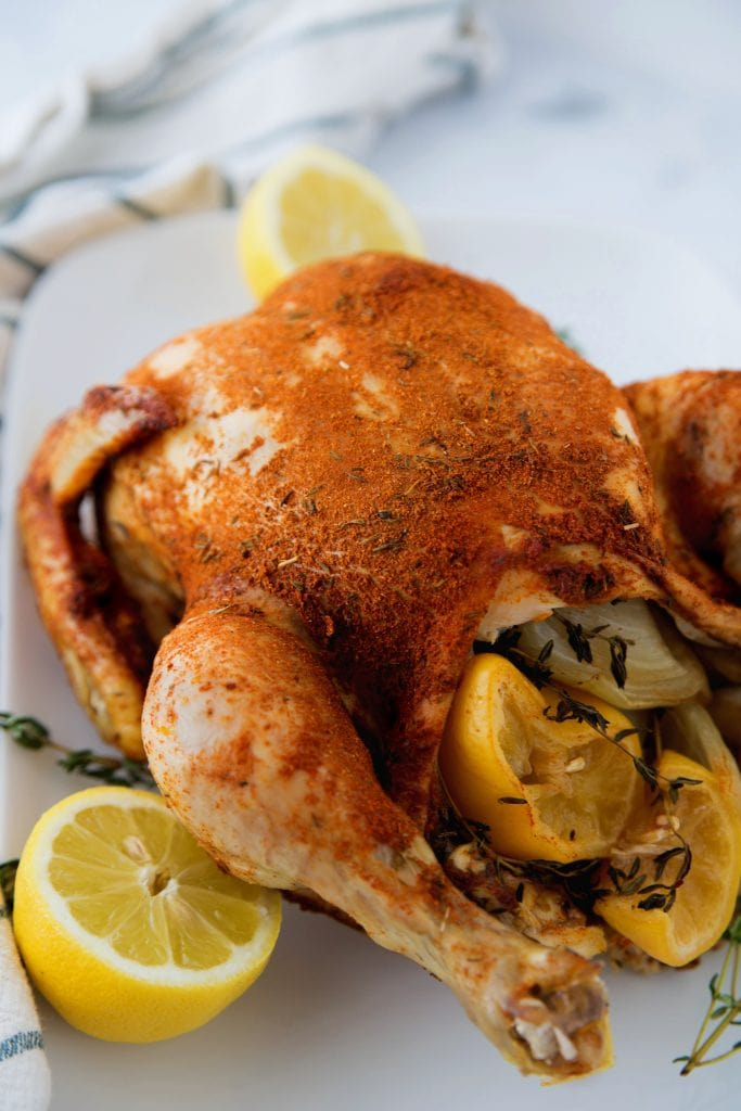 Whole spice rubbed chicken made in the Instant Pot, stuffed with lemons and onion with a white background