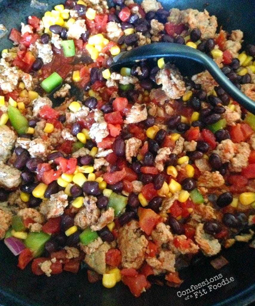 Turkey Taco Skillet filled with ground turkey, diced tomatoes, corn, black beans, and diced green peppers with a black serving spoon resting in the middle.