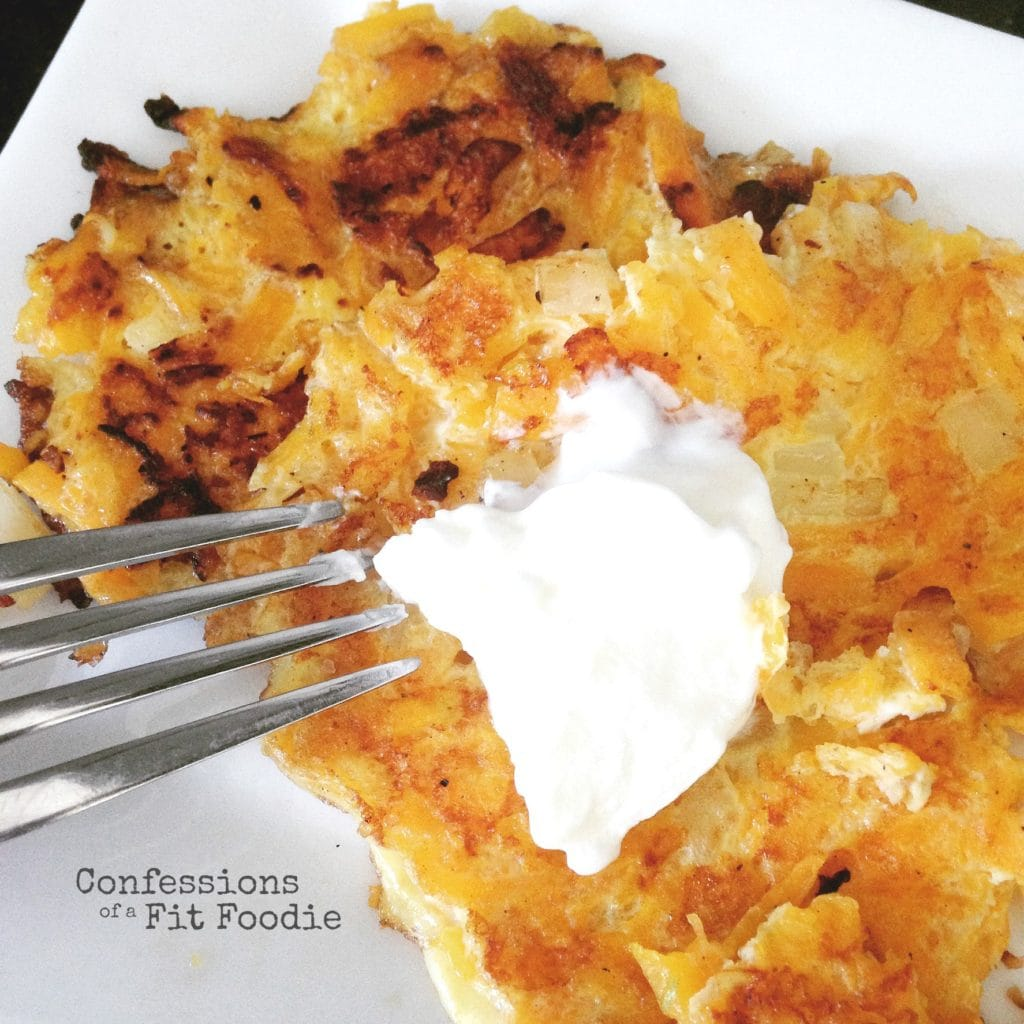 Two Butternut Squash Latkes topped with Greek yogurt are on a white plate with a fork on the side.