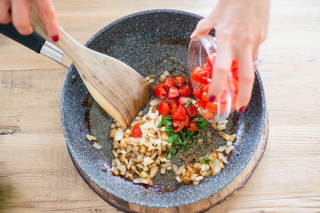A woman is mixing tomatoes, garlic, onions, and basil in a pan on a wooden table.