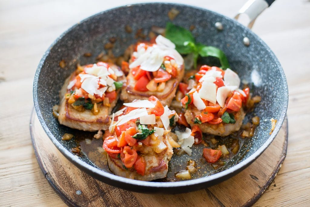 A pan with for 21 Day Fix Italian Pork Chops topped with tomatoes, basil, garlic, onions and parmesan cheese.