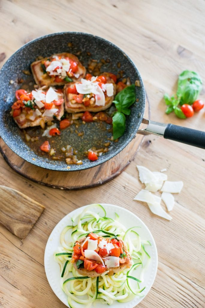 Skillet with three Italian Pork Chops topped with tomatoes, fresh basil, garlic, onions and parmesan cheese. A small white plate is nearby with a pork chop over zucchini noodles.