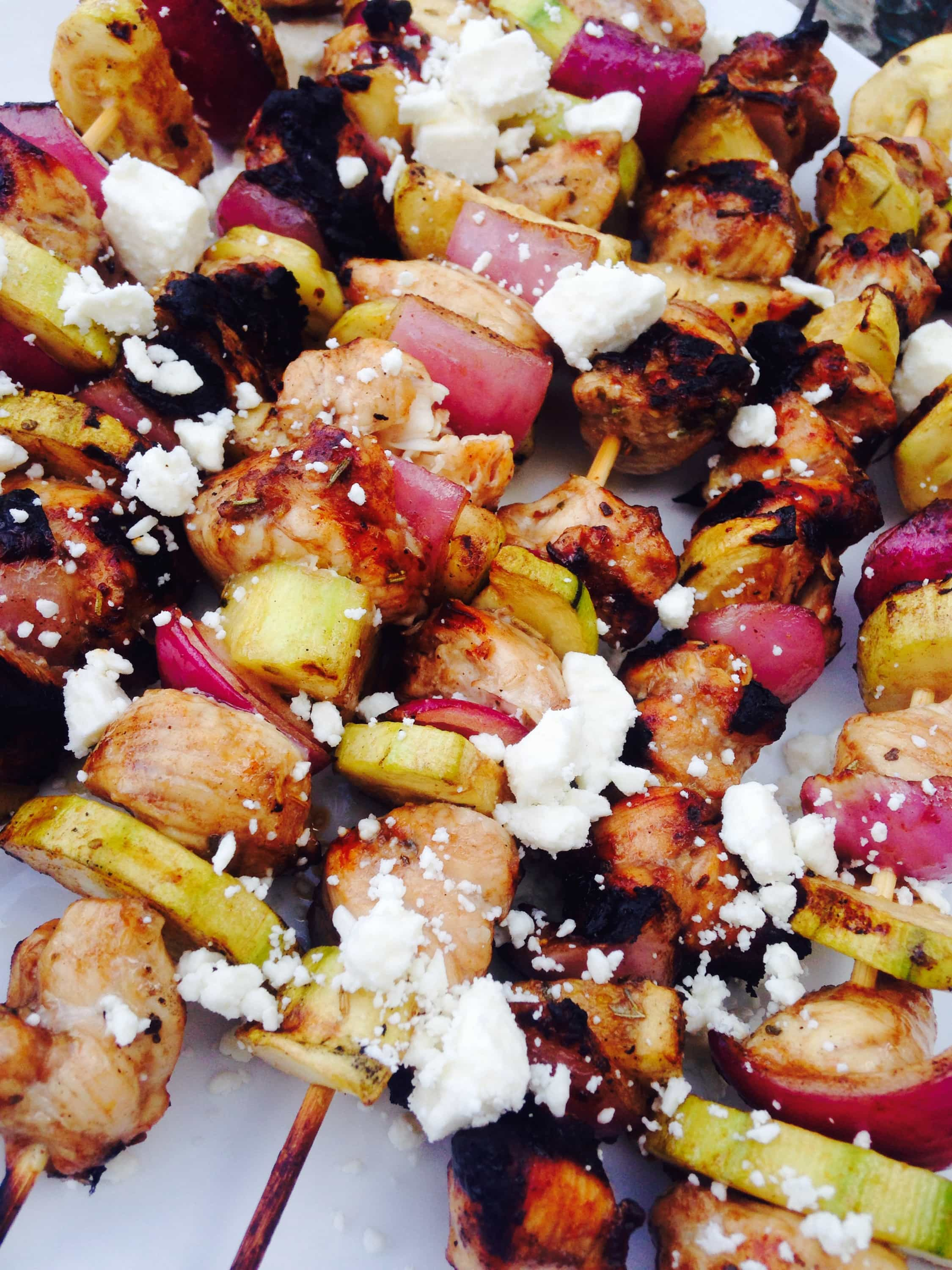 Balsamic marinated chicken, zucchini, and red onion are alternated on skewers and grilled, then topped with feta.