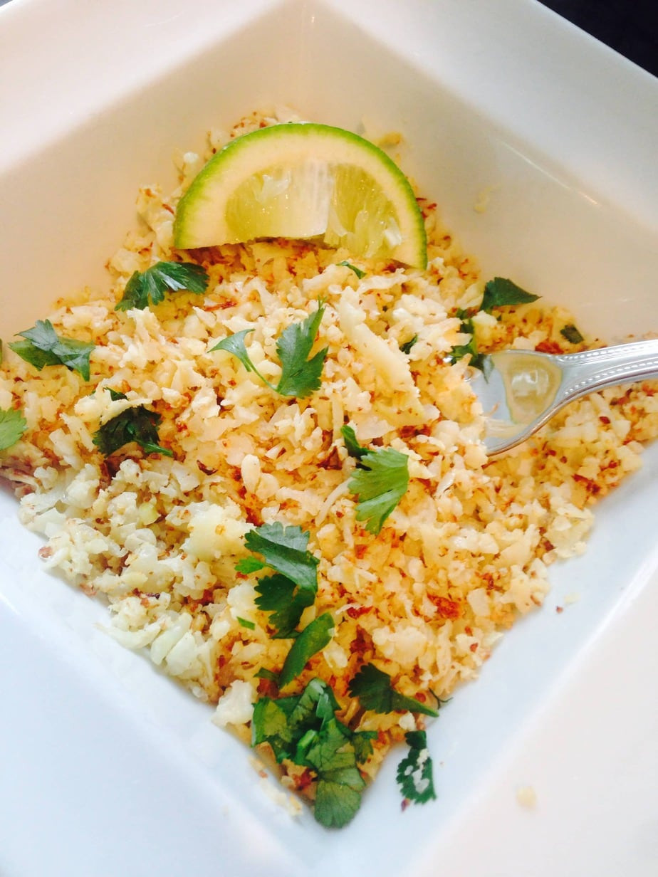 Cilantro lime cauliflower rice in a square bowl with a lime wedge and fork resting on the side