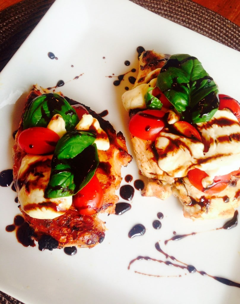 Two chicken breasts topped with tomatoes, sliced mozzarella, and basil drizzled with balsamic reduction. Some sauce is drizzled on the white square plate also.