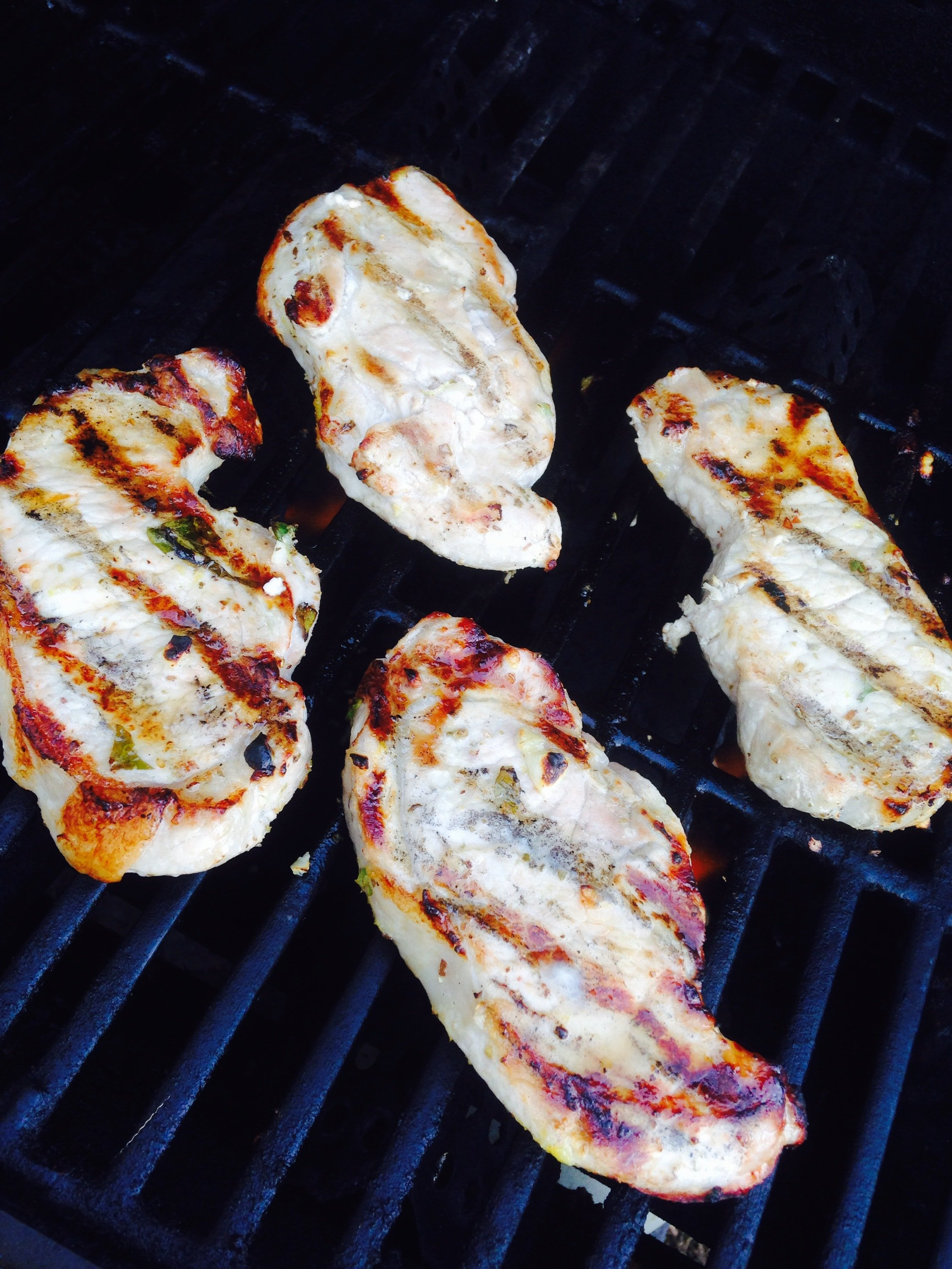 4 porkchops with grill marks lying on the grill