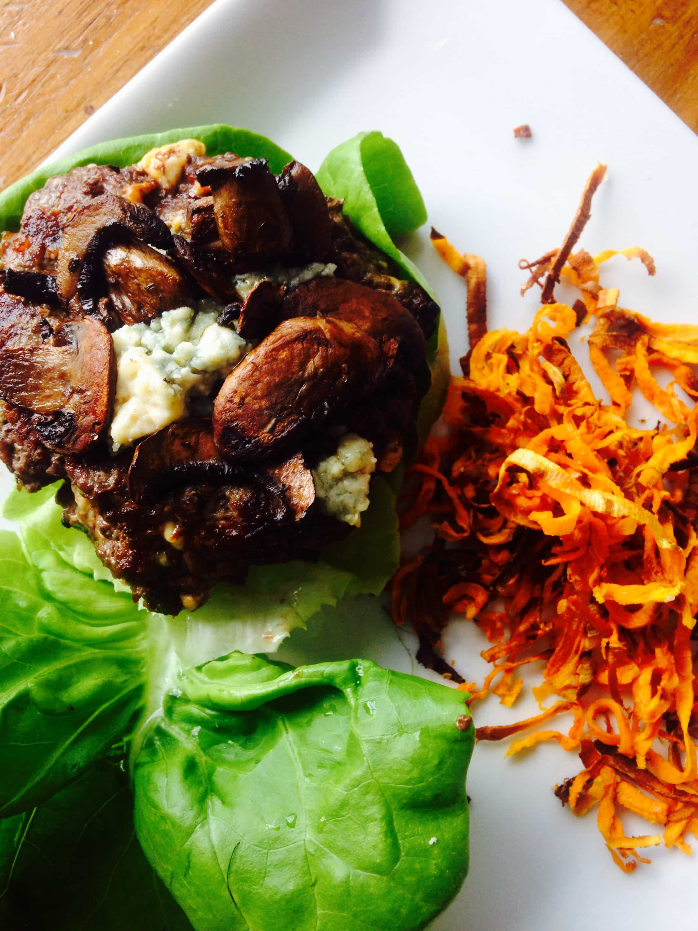 """Blue cheese stuffed cheeseburger topped with mushrooms on a lettuce wrap """"bun"""" plated with shoestring sweet potato fries."""