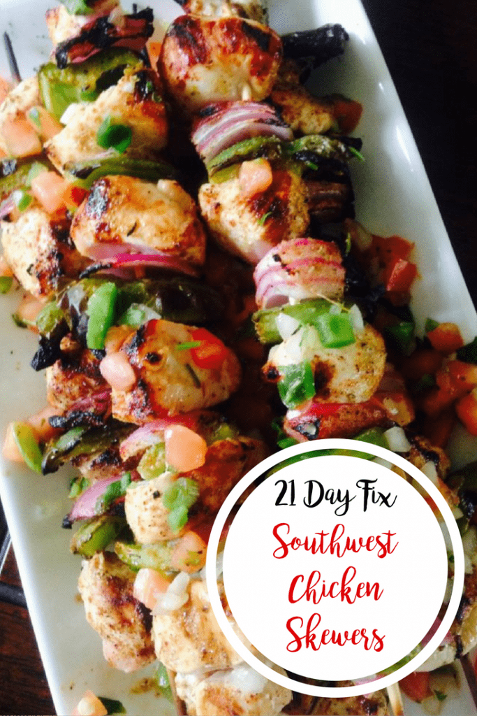 Grilled southwest chicken, green pepper, and red onion alternate on wooden skewers. Many are piled on a long rectangular plate with a dark background and text overlay- 21 Day Fix Southwest Chicken Skewers