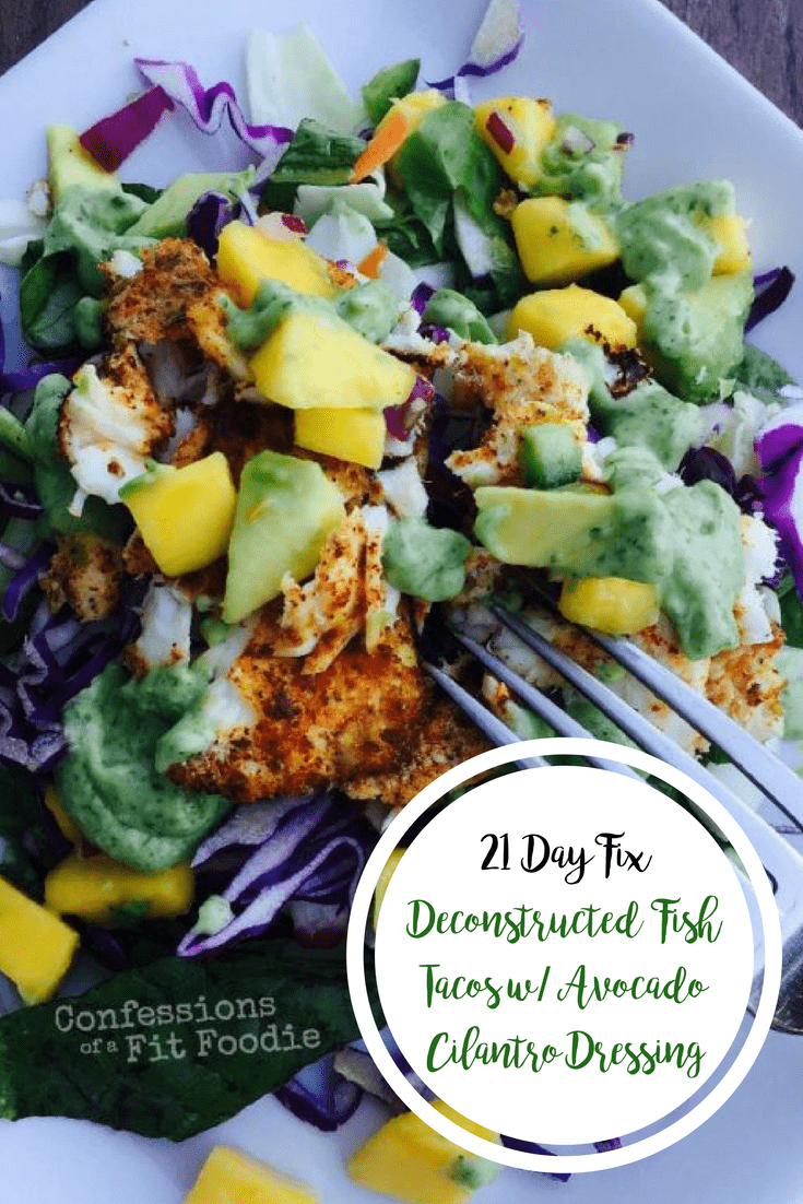 Fish taco salad with red cabbage, diced mango, diced avocado, taco seasoned fish, and greens on a square white plate and a fork poised for eating and the text overlay- 21 Day Fix Deconstructed Fish Tacos w/ Avocado Cilantro Dressing