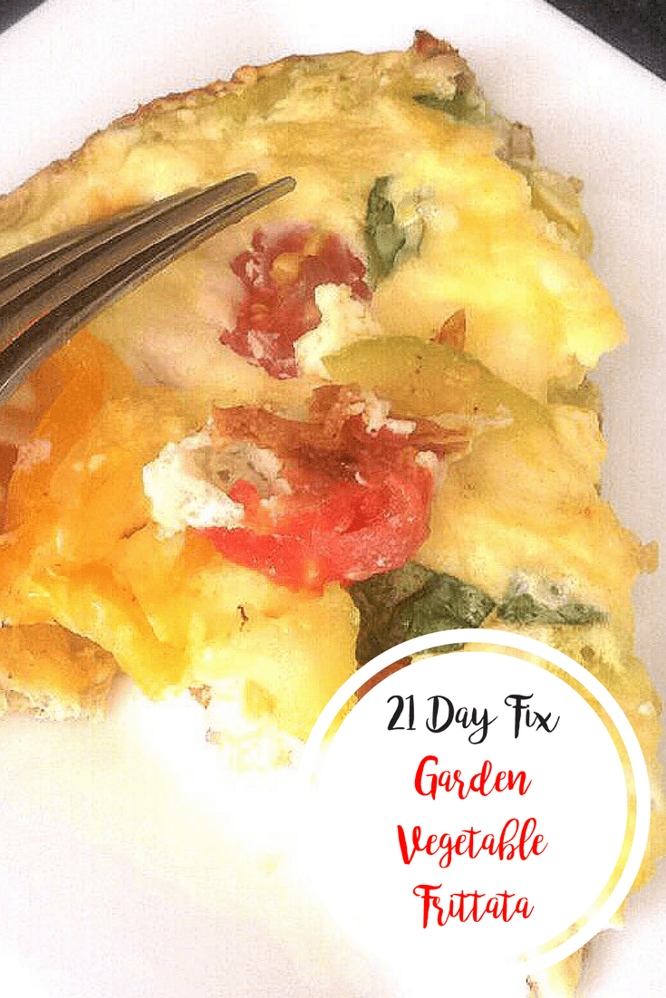 A triangular slice of fritatta on a white plate with tomatoes, zucchini, and basil peeking through the egg dish- with the text overlay 21 Day Fix Garden Vegetable Frittata