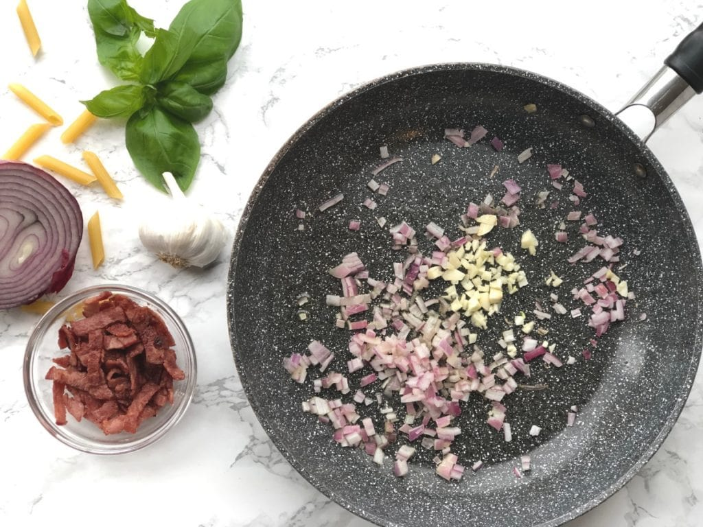 Skillet with red onion, garlic, bacon and basil on the side