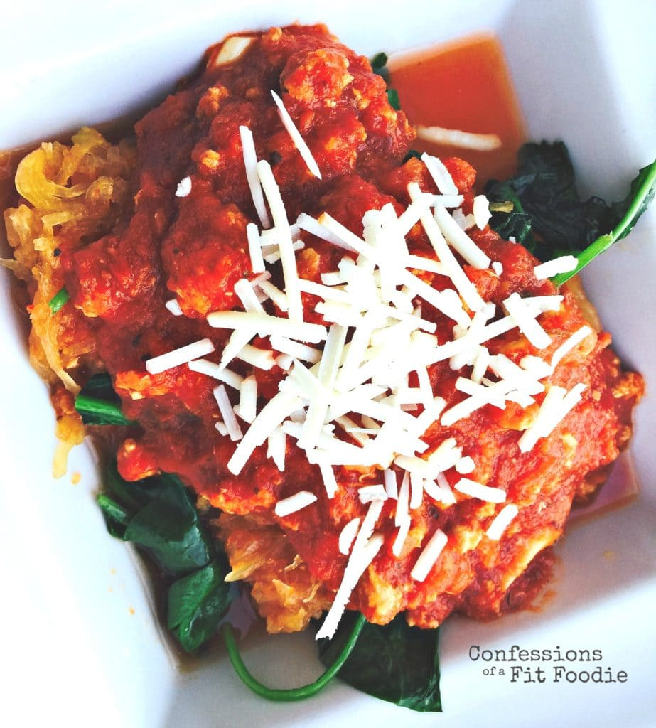 Overhead photo of spaghetti squash topped with meat sauce, spinach, and shredded parmesan cheese.