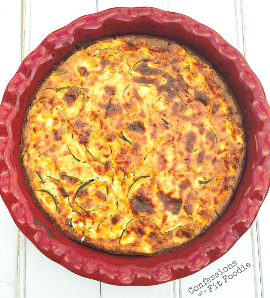 Overhead view of crustless zucchini quiche, a recipe from the blog Confessions of a Fit Foodie, served in a red round pie plate