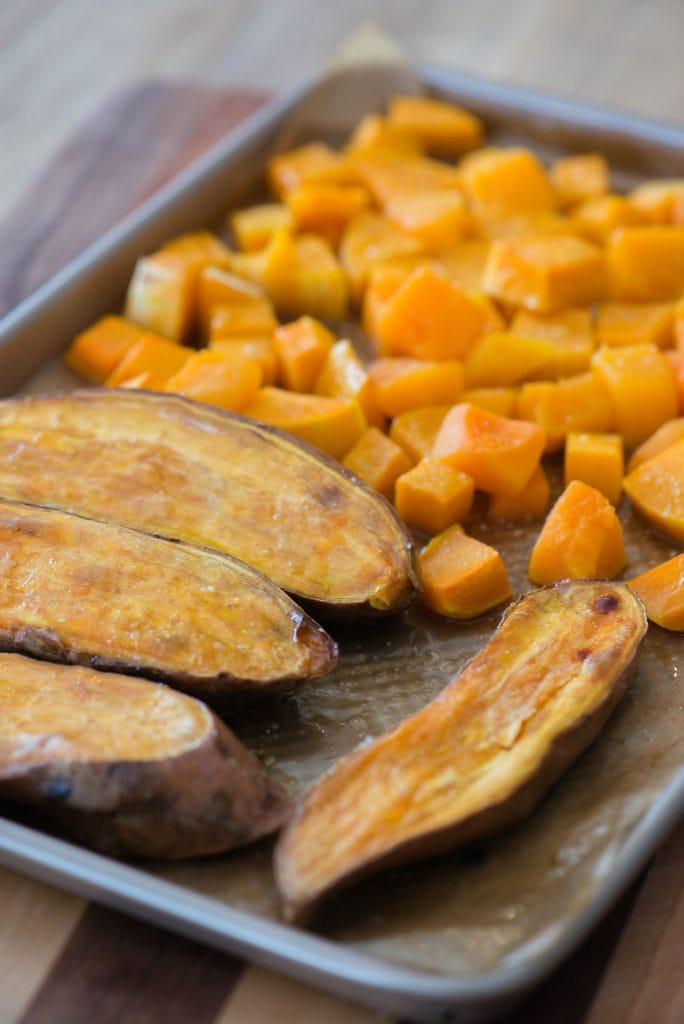 A sheet pan with sweet potatoes and butternut squash cubes