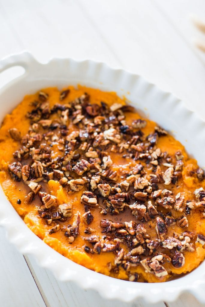 Close up photo of healthy sweet potato casserole in a white oval baking dish on a white wooden background. The mashed sweet potatoes are topped with a toasted pecan streussel.