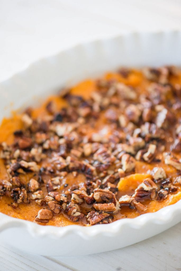 White casserole dish with a healthy sweet potato casserole topped with pecans on a white wooden table.