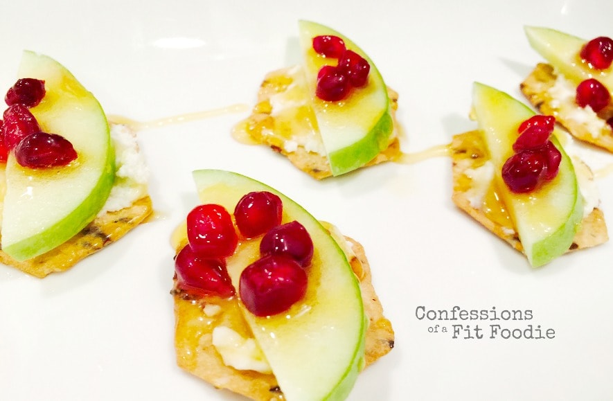 Close up of gluten free crackers topped with goat cheese, a slice of granny smith apple, pomegranate seeds, and drizzled with honey on a white plate