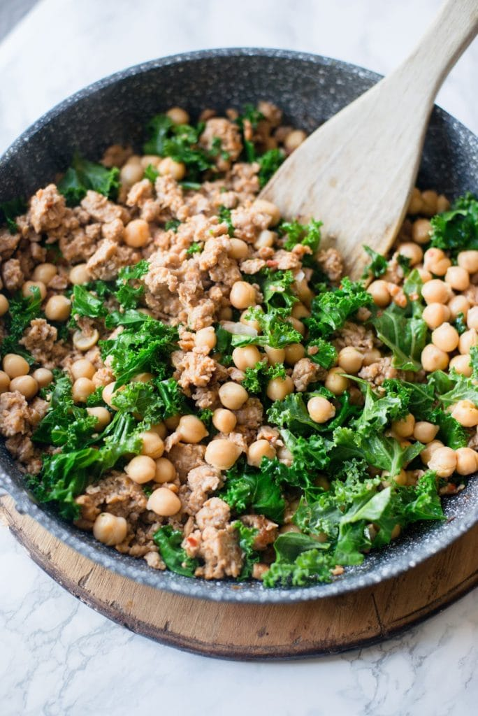 A Skillet is shown with italian chicken sausage, chick peas, and kale.