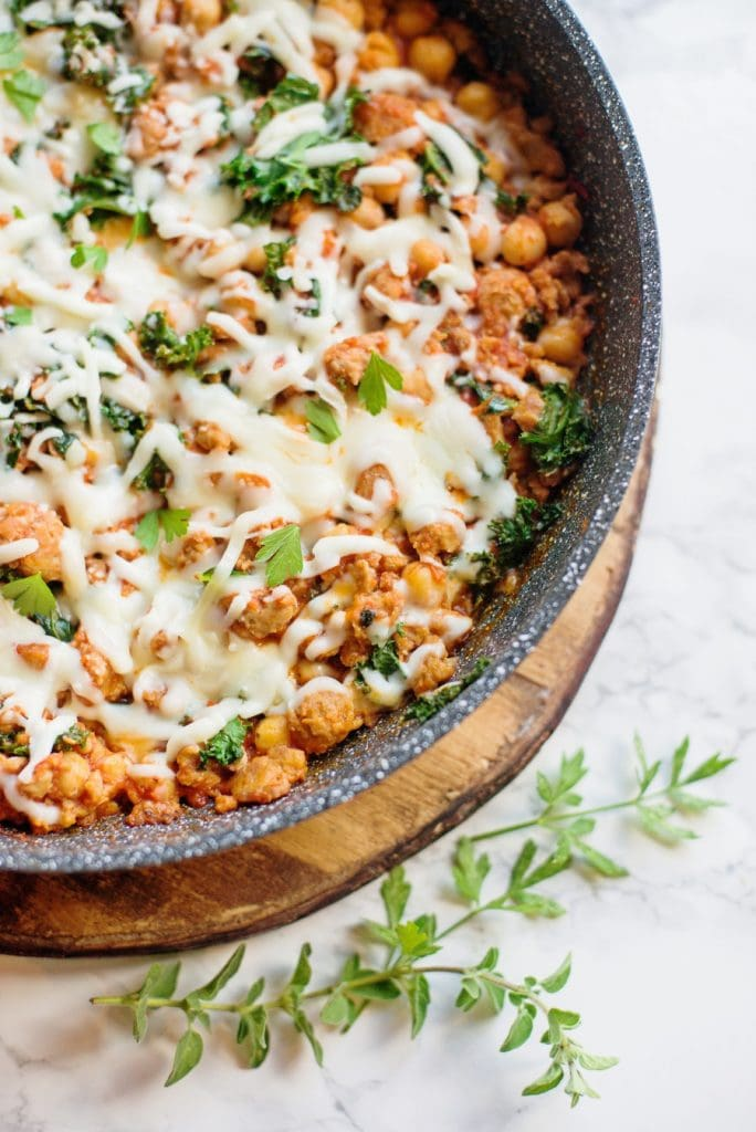 Healthy sausage bean and kale skillet topped with cheese sitting on a marble background.