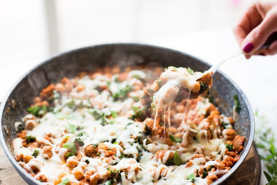 A warm from the stove photo of 21 Day Fix Sausage Bean and Kale Skillet topped with mozzarella cheese.