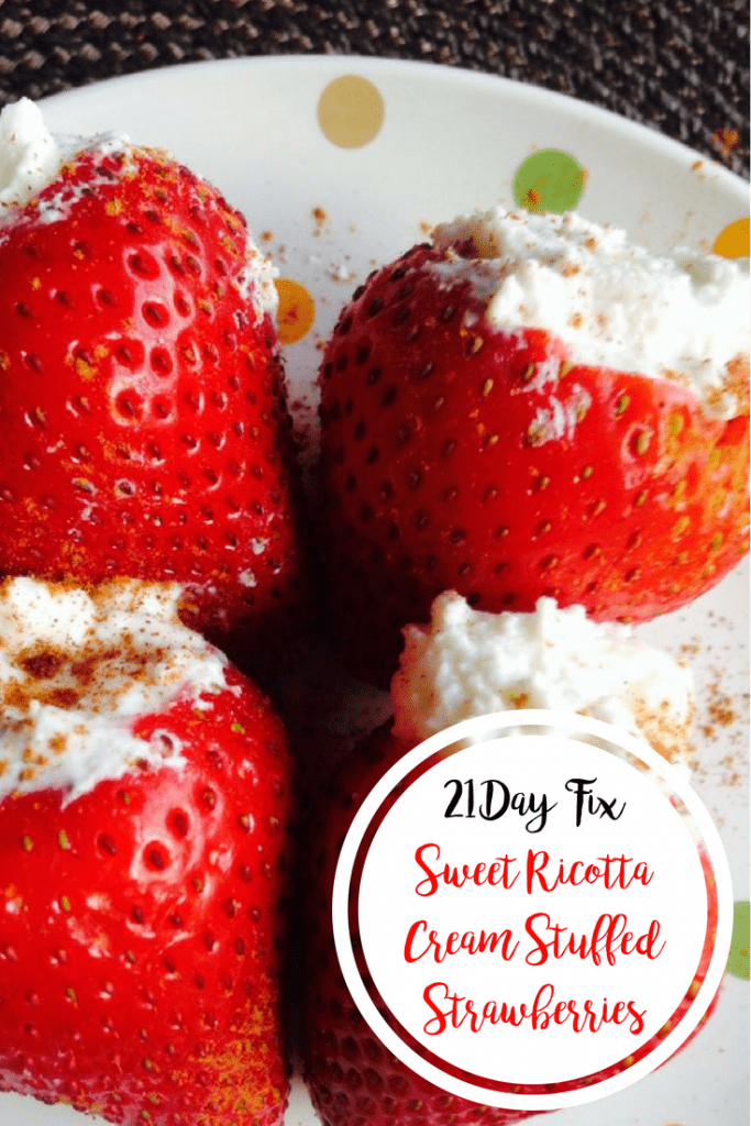 4 strawberries stuffed with sweet ricotta, topped with cinnamon on a white and colored polka dot plate with a black background- with the text overlay 21 Day Fix Sweet Ricotta Cream Stuffed Strawberries in a white circle