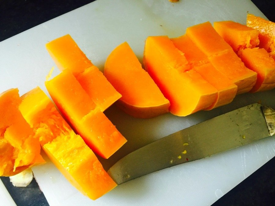Sliced butternut squash on a white cutting board with a chef's knife