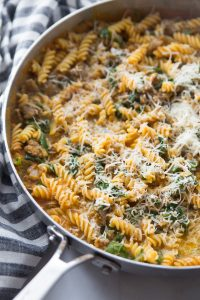 large saucepan with pumpkin pasta and spicy sausage topped with shredded parmesan cheese. pan is resting on a blue and white checkered napkin.