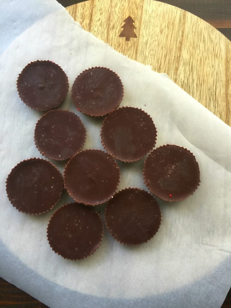 Chocolate peanut butter cup fudge circles on a piece of parchment paper on a wooden background.