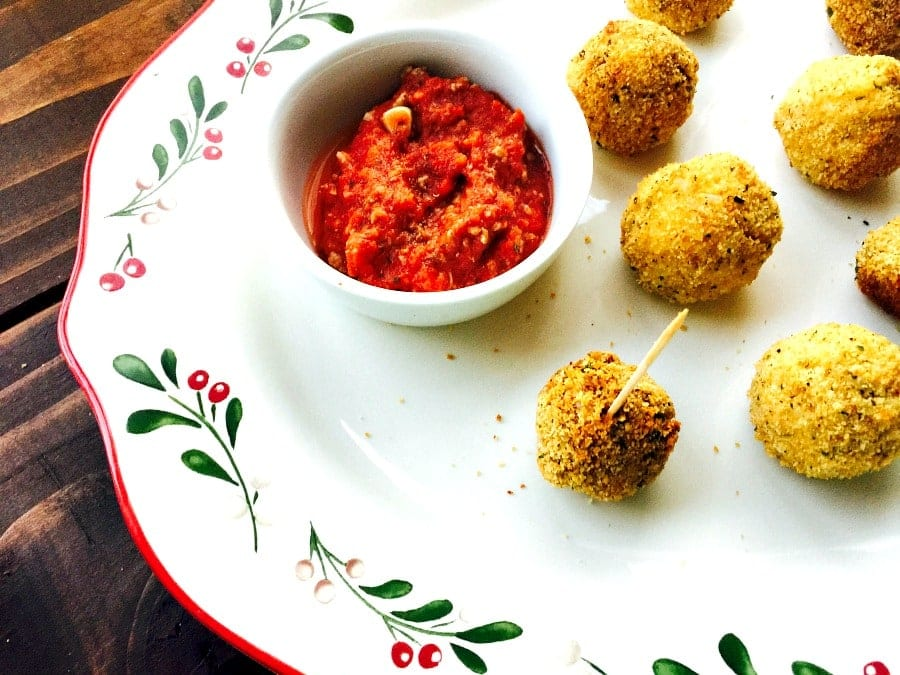 Close up of Mini Arancini Rice Balls on a white, red, and green Christmas Platter with Marinara Sauce for dipping on the side.