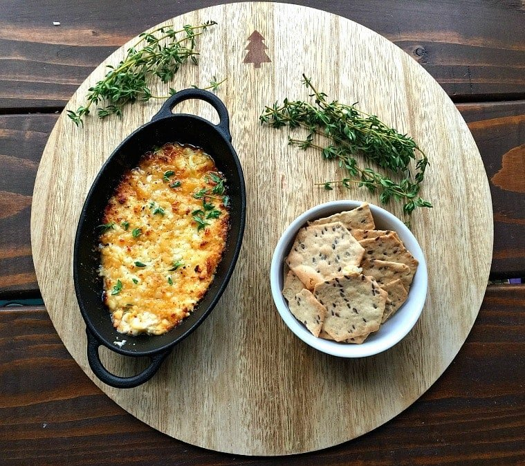Cast iron pan of baked feta dip next to a white bowl of gluten free crackers on a wooden round, garnished with thyme.