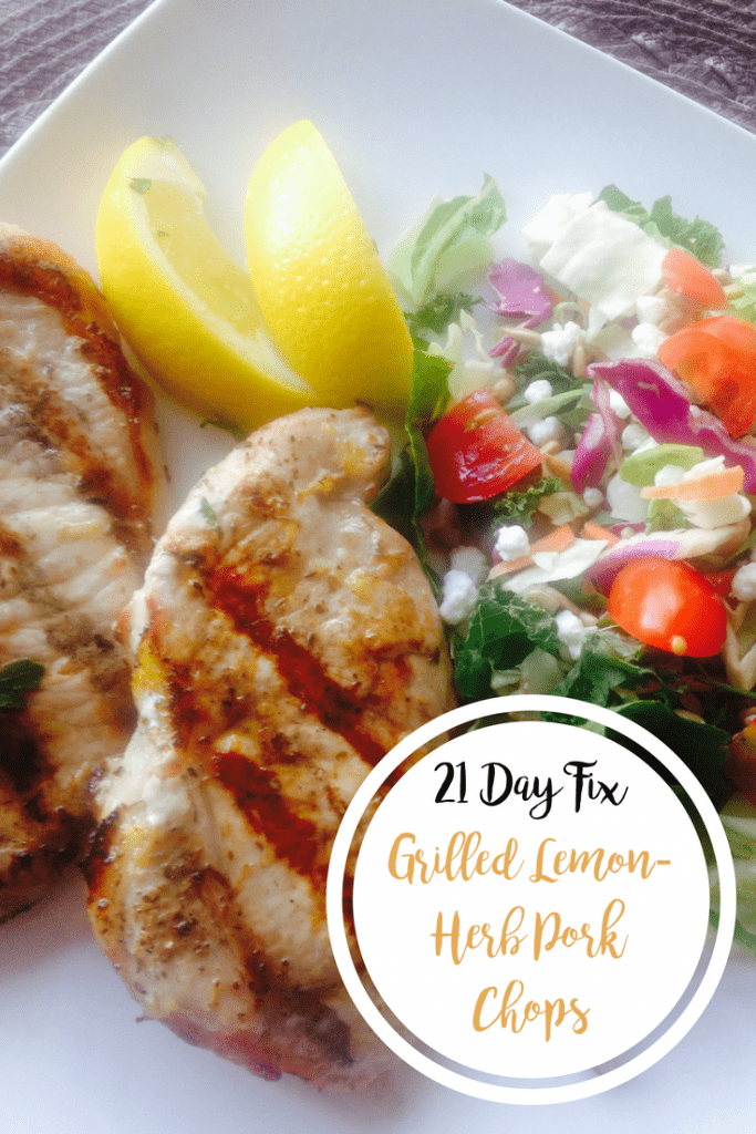 Two Grilled Lemon-Herb Pork Chops next to a side salad and lemon wedges on a square white plate with the text overlay- 21 Day Fix Grilled Lemon-Herb Pork Chops