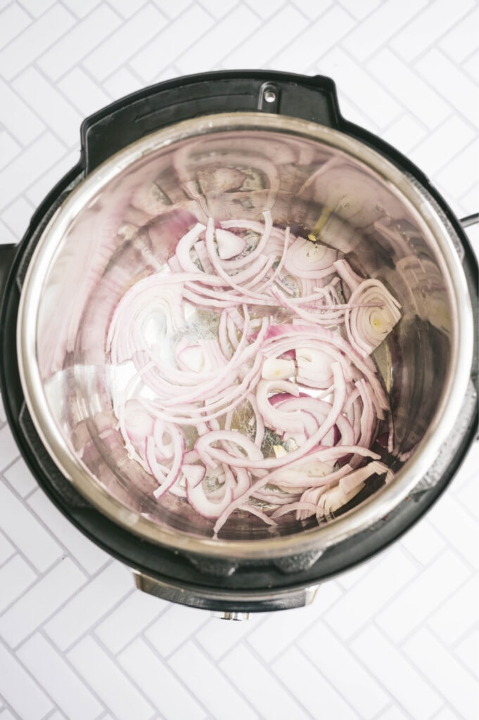 Overhead photo of red onion sauteing in the instant pot on a white tile surface.