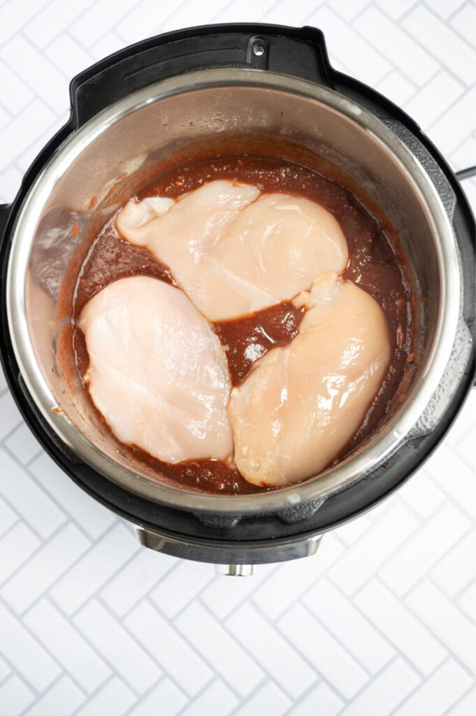 Overhead photo of an Instant Pot full of balsamic chicken ingredients, including chicken on the top.