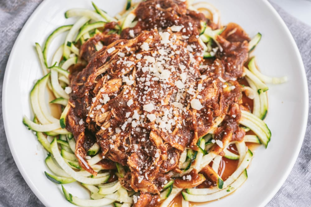 Close up photo of zoodles topped with Instant Pot Balsamic chicken, sprinkled with parmesan cheese. These are on a white plate with a gray linen background.