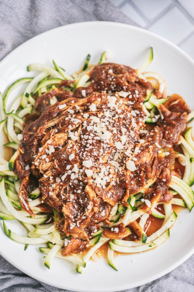 A white plate of balsamic chicken with zoodles topped with parmesan cheese on a gray dish towel.