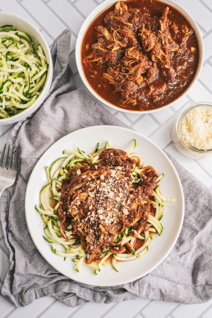 Overhead photo of balsamic chicken with zoodles on a white plate. At the top of the photo are two bowls, one filled with zoodles, the other filled with balsamic chicken. There is a small glass jar filled with parmesan cheese, too.