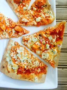 Flatbread pizza cut into triangles topped with buffalo chicken, ricotta, blue cheese, and mozzarella cheese from the blog, Confessions of a Fit Foodie.