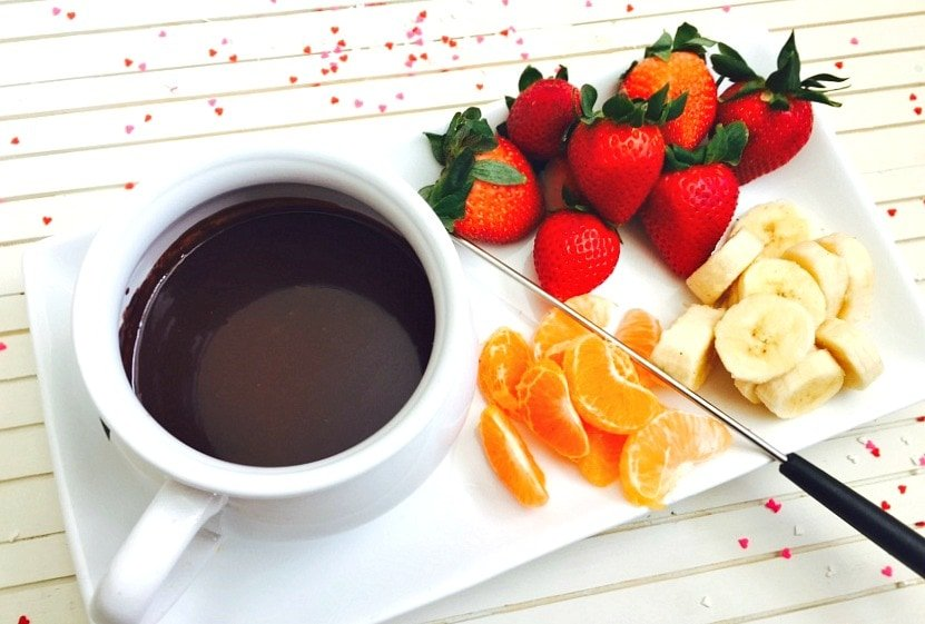 A small white pot of dairy free chocolate fondue on a white rectangular serving dish. On the dish are whole strawberries, sliced bananas, and mandarin orange segments. There are small pieces of heart shaped confetti on the white wooden background.