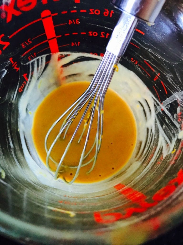 Overhead photo of a glass measuring bowl with a metal whisk mixing citrus maple dijon dressing to top turkey burgers.