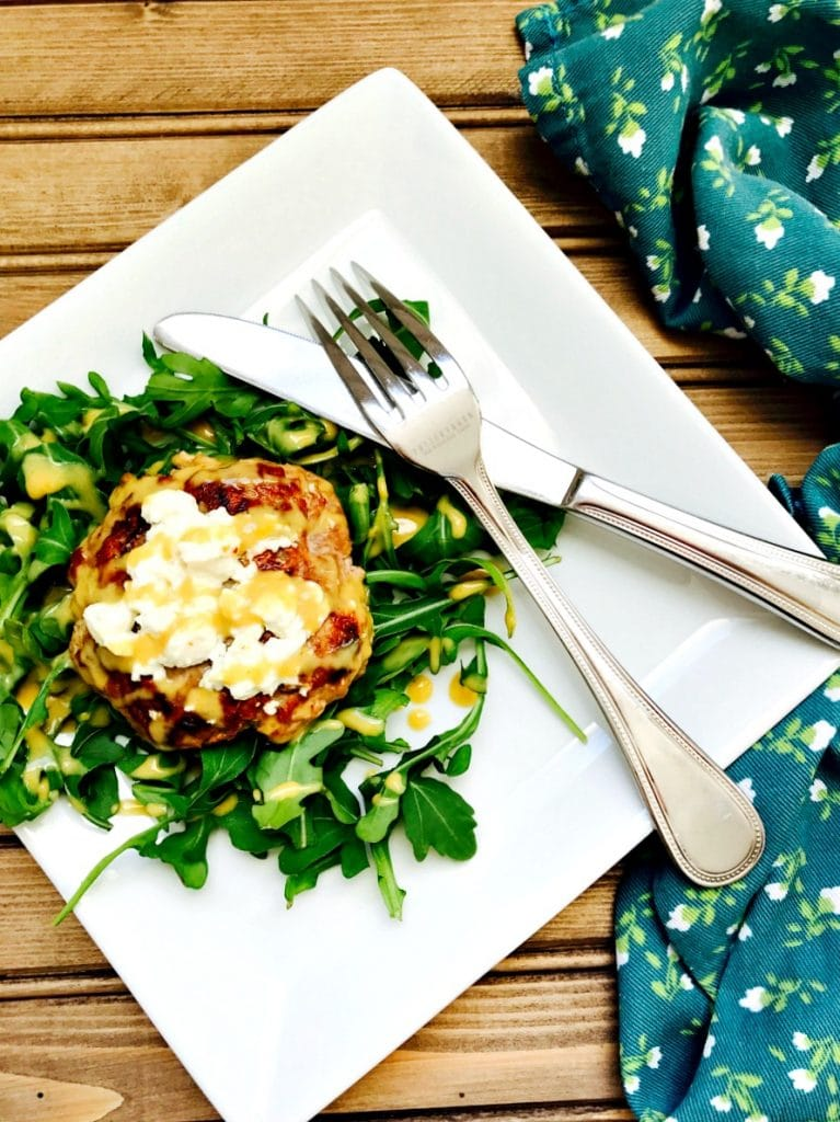 Simple and Delicious 21 Day Fix approved Turkey Burger with Warm Goat Cheese and a Citrus Maple Dijon Dressing on a white plate on a wooden surface.  Off to the side is a dark blue flowered cloth.