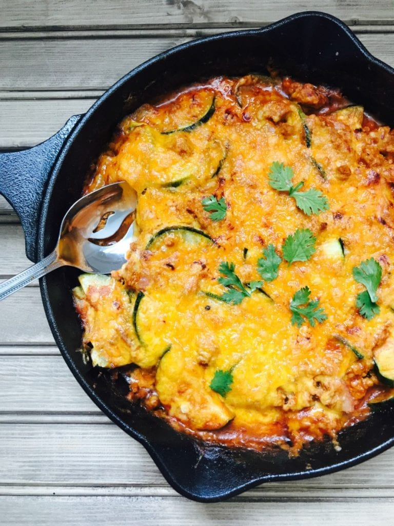 Cast iron skillet on wooden background filled with zucchini and ground meat, topped with cheese and cilantro.  A serving spoon is poised on the side, ready to dig in.