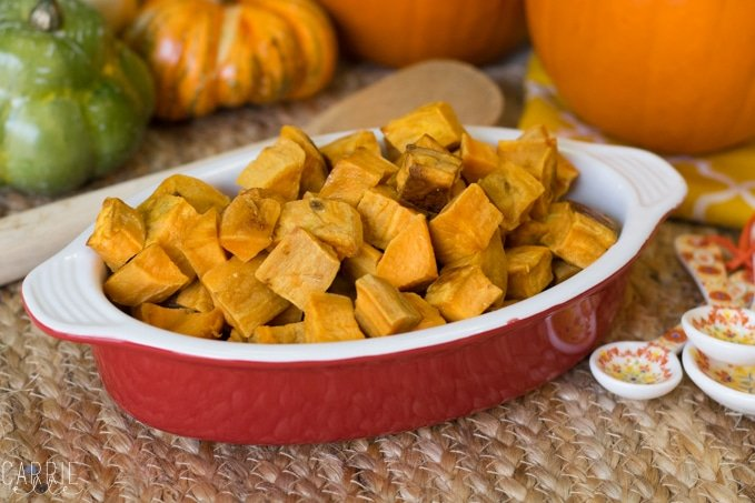 Savory diced sweet potatoes in a red ceramic serving dish with pumpkins in the background