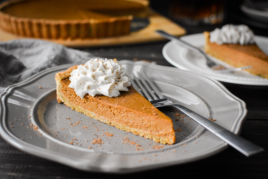 Slice of Pumpkin custard tart with whipped topping on gray plate with whole tart in the background