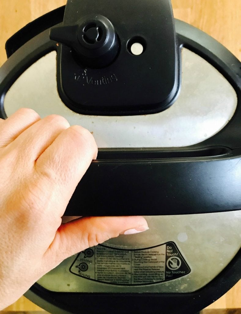 Overhead photo of an instant pot lid with a person's hand on the handle