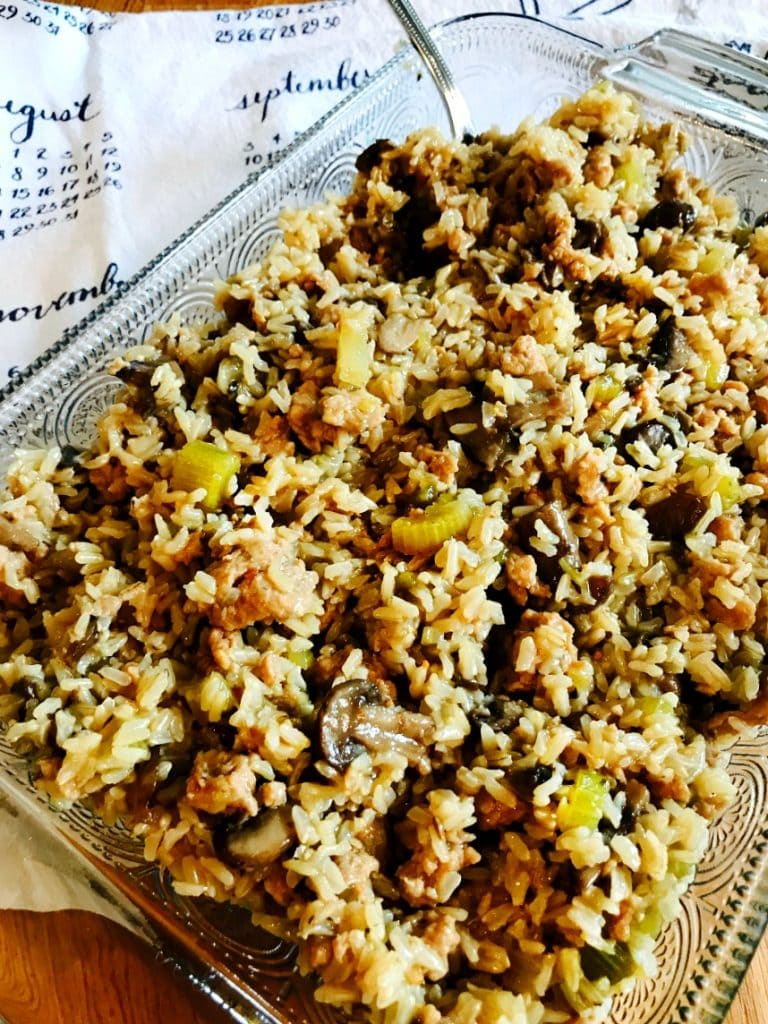 Close up photo of brown rice and sausage stuffing in a glass baking dish. There is a white and blue calendar tea towel in the background.